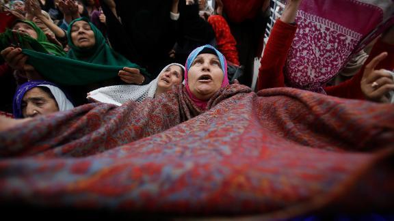 A Kashmiri Muslim woman raises her veil in the air to pray in Srinagar, India, on November 10, 2019.