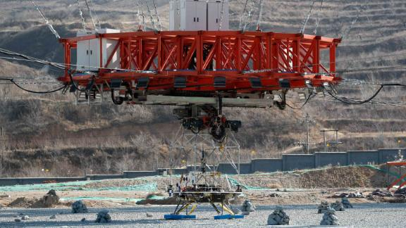 The lander sits before being lifted for tests of its hovering, obstacle avoidance and deceleration capabilities.