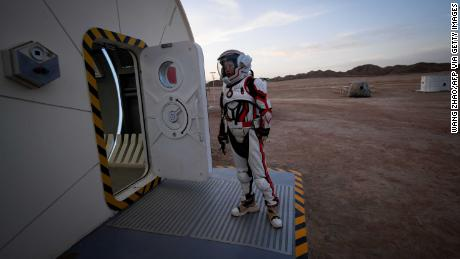 "This picture taken on April 17, 2019 shows a woman wearing a spacesuit walking out of ""Mars Base 1"", a C-Space Project, in the Gobi desert, some 40 kilometres from Jinchang in China's northwest Gansu province.  Surrounded by barren hills in northwest Gansu province, ""Mars Base 1"" opened to the public on April 17 with the aim of exposing teens -- and soon tourists -- to what life could be like on the planet."