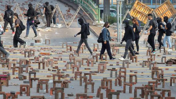 Protesters walk past barricades of bricks on a road near the Hong Kong Polytechnic University on November 14.