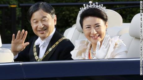 The Japanese Emperor Naruhito and Empress Masako wave to the crowd during his enthronement parade from the Imperial Palace to the Imperial Residence Akasaka in Tokyo on November 10, 2019.