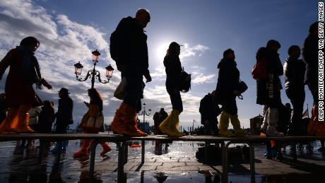 People cross the Reva degli Shiavoni Bridge on November 14, 2019 in Venice.