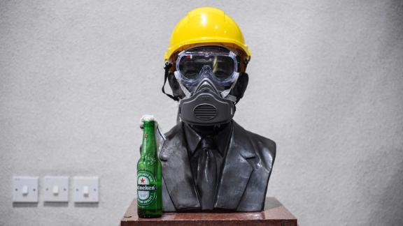 A Molotov cocktail, a gas mask and a yellow construction helmet are placed upon a bust of late hotel tycoon Hui Yeung Shing at the campus of The Chinese University of Hong Kong on November 13.