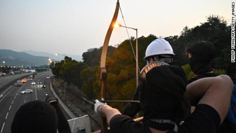 "A protester uses an arrow to guide cars on the Tolo Highway outside the Chinese University of Hong Kong (CUHK), in Hong Kong on November 13, 2019. - Pro-democracy protesters stepped up on November 13 a ""blossom everywhere"" campaign of road blocks and vandalism across Hong Kong that has crippled the international financial hub this week and ignited some of the worst violence in five months of unrest. (Photo by Philip FONG / AFP) (Photo by PHILIP FONG/AFP via Getty Images)"