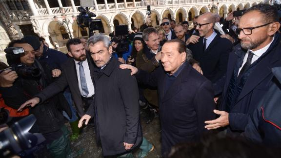 Head of the Forza Italia party and former Italian Prime Minister Silvio Berlusconi, second from right, assesses the flood damage on November 14.
