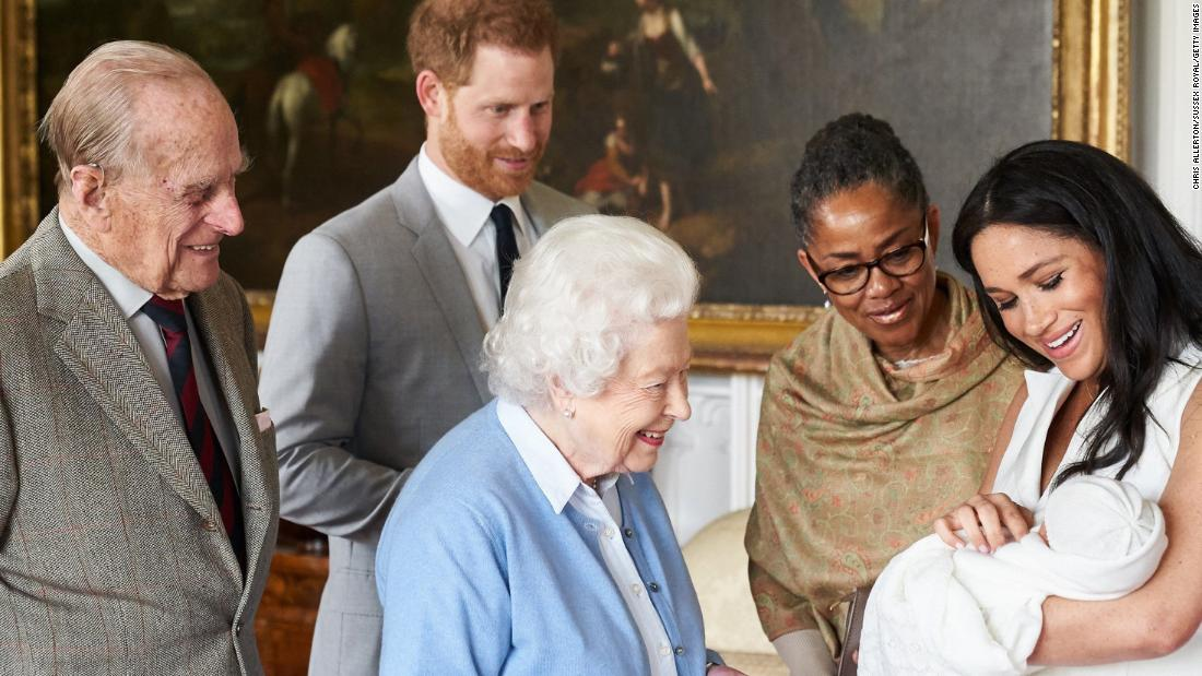 "The Queen looks at <a href=""http://www.cnn.com/2019/05/08/uk/gallery/archie-royal-baby-harry-meghan/index.html"" target=""_blank"">her new great-grandchild, Archie,</a> in May 2019. Archie is the first child of Prince Harry, second from left, and his wife Meghan, the Duchess of Sussex. Prince Philip is on the far left. Meghan's mother, Doria Ragland, is next to her at right."