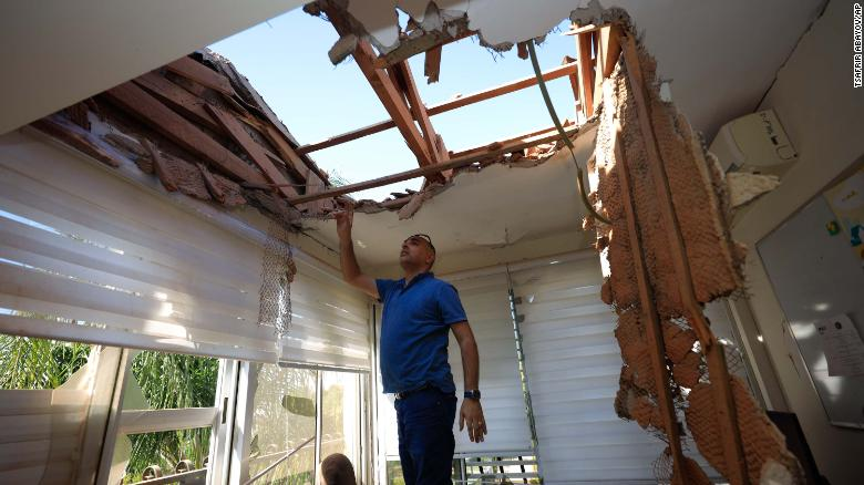 A man looks at the damage to a house in Sderot, Israel, after it was hit by a rocket fired from Gaza on Tuesday.