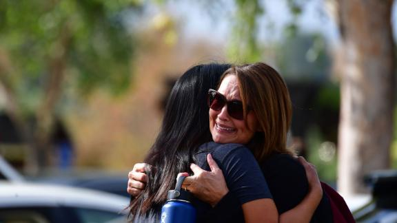 """Women embrace in Central Park after a shooting at Saugus High School in Santa Clarita, California on November 14, 2019. - At least four people were injured in a shooting at a high school north of Los Angeles Thursday, triggering a police hunt for the suspect who was later taken into custody.Police and ambulances swarmed the area around Saugus High School in Santa Clarita, 40 miles (65 kilometers) north of Los Angeles, after the early morning shooting sent panicked children running from the area. """"Update regarding the shooting at #SaugusHigh, suspect is in custody and being treated at a local hospital,"""" tweeted Los Angeles Country Sheriff Alex Villanueva. The suspect was described as a male Asian. Local media reports said he was 15 years old. Aerial video from the local NBC affiliate showed students with hands raised being escorted by officers from the building, and led to a nearby church, as others stood outside the perimeter on their cell phones. (Photo by Frederic J. BROWN / AFP) (Photo by FREDERIC J. BROWN/AFP via Getty Images)"""
