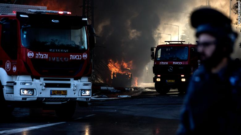 Firefighters at a factory that was hit by a rocket in Sderot, Israel on Tuesday.