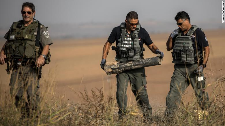 Israeli police sappers remove a rocket fired from the Gaza Strip in farmland near the border on Wednesday.