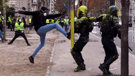 A demonstrator collides with riot police in Paris on December 1, 2018.