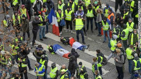Demonstrators wrapped in French flags lie on the grounds of riot police on the Champs Elysées on 8 December 2018.