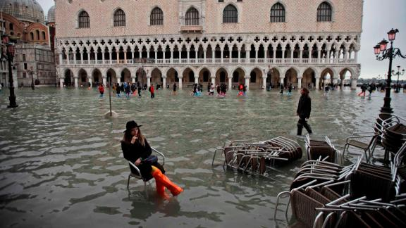 A woman sits in a chair in a flooded St. Mark's Square on November 13.