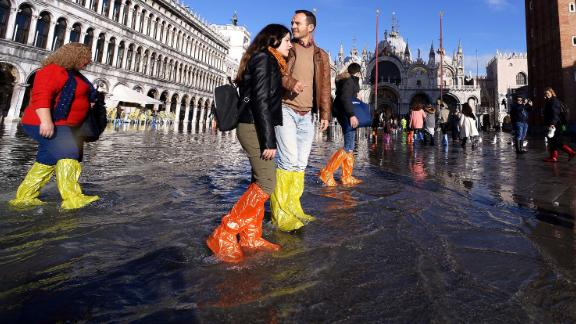 People wearing waterproof shoe covers walk through floodwater on Thursday, November 14, at St. Mark's Square in Venice, Italy.