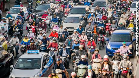 HANOI, VIETNAM - NOVEMBER 04:  Motorbike drivers covered-up with face masks try to get through the morning peak hour traffic at Nga Tu So intersection on November 4, 2016 in Hanoi, Vietnam. Hanoi is ranked as one of the most polluted city in Southeast Asia with the air quality monitor installed by U.S. Embassy in the city center often shows Air Quality Index (AQI) of over 200 at day time, listed as √¢ 'Very Unhealthy'. The main cause of this air pollution is over 5.3 million motorbikes and 560,000 cars in the traffic of Hanoi while figures continue to increase every year, according to reports. Vietnam's motorbike culture has taken over the bicycle in the capital, known to be one of the world's fastest expanding economy which resulted in the masks and gloves being a common sight in the tropical city, both to reduce inhalation of motorbike fumes and Vietnamese women to protect themselves from the sun. (Photo by Linh Pham/Getty Images)