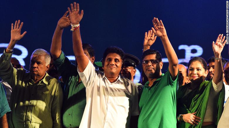 Presidential candidate Sajith Premadasa (center) and Sri Lanka's Prime Minister Ranil Wickremesinghe (left) wave to supporters as they attend a campaign rally in the Sri Lankan capital of Colombo on November 13, 2019.