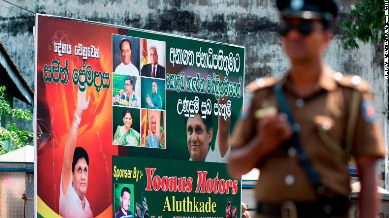 A policeman stands guard at a roadblock near an electoral poster of deputy leader of the ruling United National Party (UNP) and New Democratic Front presidential candidate Sajith Premadasa before a campaign rally in Colombo on November 13, 2019.