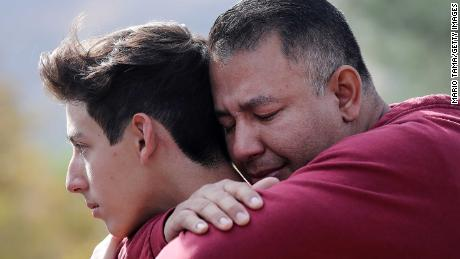 SANTA CLARITA, CALIFORNIA - NOVEMBER 14: Marco Reynoso (R) hugs his son, 11th-grader Dylan Reynoso, after reuniting at a park near Saugus High School after a shooting at the school left two students dead and three wounded on November 14, 2019 in Santa Clarita, California. A suspect in the shooting is being treated at a local hospital for a gunshot wound to the head.  (Photo by Mario Tama/Getty Images)
