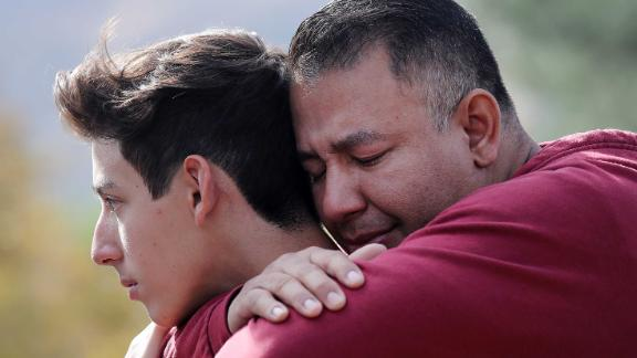 Marco Reynoso, right, hugs his son, 11th-grader Dylan Reynoso, after reuniting at a park near Saugus High School.