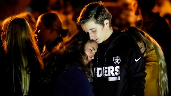 Hannah Schooping-Gutierrez, center, a student at Saugus High School, is comforted by her boyfriend, Declan Sheridan, a student at nearby Valencia High School, during a vigil at Central Park in Santa Clarita.