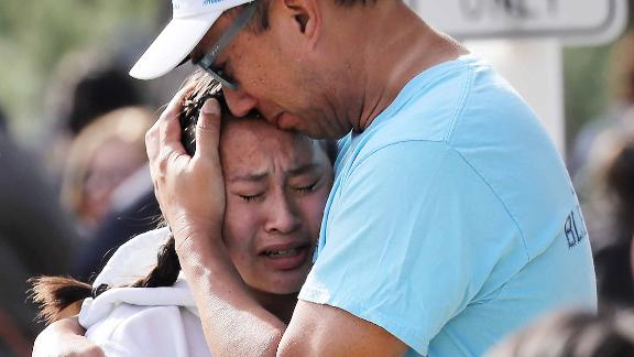 A father hugs his daughter after being reunited at a park near Saugus High School.