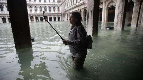 A woman with a selfie stick makes her through a flooded St. Mark's Square.