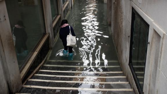 People wade Friday through a flooded Venice alley.