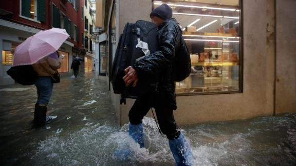 A man carries luggage Friday as he wades through the flood.