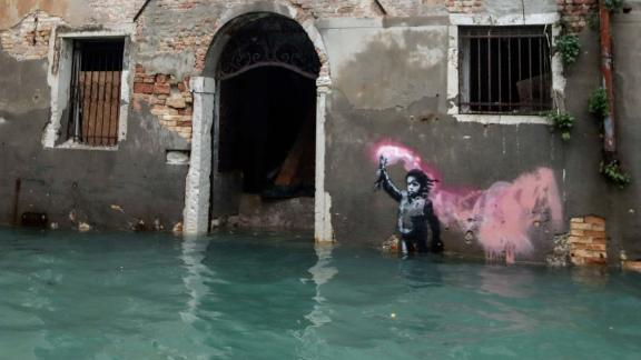 Banksy's migrant child mural is seen partially submerged on Friday.