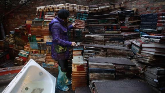 "A woman checks the state of books from renowned bookstore ""Acqua Alta"" (High Water) on Friday after flooding in Venice."