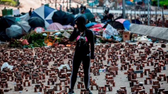 A protester (C) stands amongst bricks placed on a barricaded street outside The Hong Kong Polytechnic University in Hong Kong on November 15, 2019.