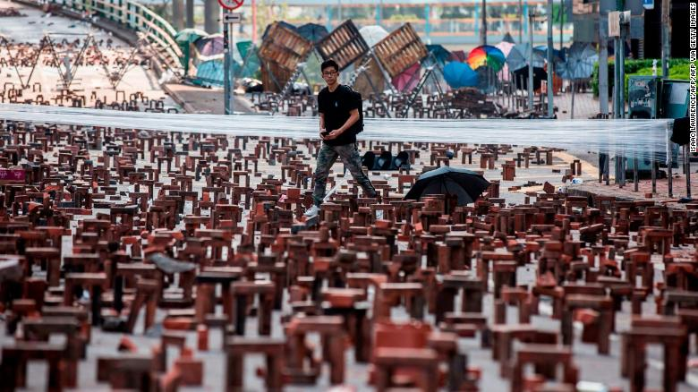 A man walks through bricks placed on a barricaded street outside The Hong Kong Polytechnic University in Hong Kong on November 15, 2019.