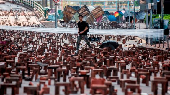A man walks through bricks placed on a barricaded street outside The Hong Kong Polytechnic University in Hong Kong on November 15, 2019.