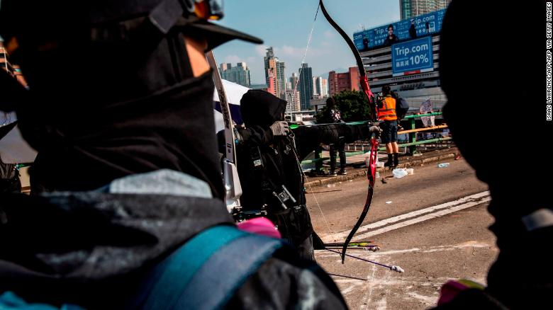 A protester uses a bow and arrow while standing on a barricaded street outside The Hong Kong Polytechnic University in Hong Kong on November 15, 2019.
