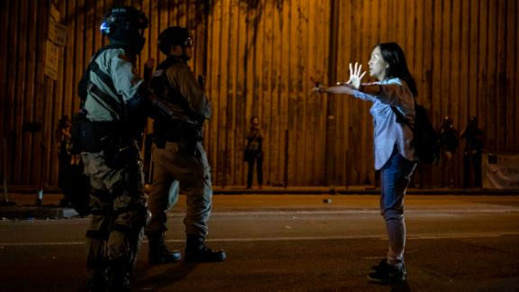 A woman tries to hold back riot police from approaching the Hong Kong University in Hong Kong on Saturday.