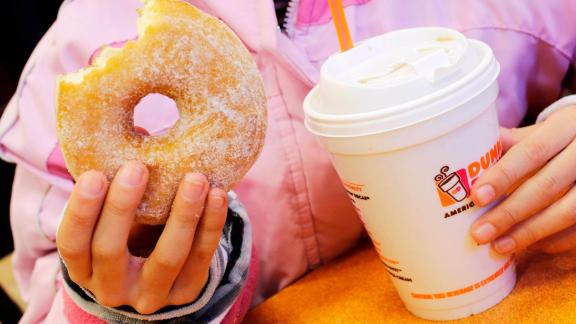 FILE- In this Feb. 14, 2013 file photo, a girl holds a beverage, served in a foam cup, and a donut at a Dunkin