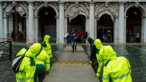 People traverse a provisional footpath built over flood waters on Friday, November 15, in Venice, Italy.