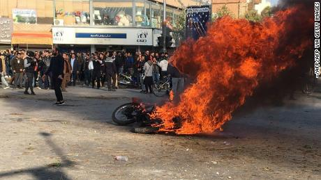 Iranian protesters gather around a burning motorcycle during a demonstration against an increase in gasoline prices in the central city of Isfahan, on November 16, 2019. - One person was killed and others injured in protests across Iran, hours after a surprise decision to increase petrol prices by 50 percent for the first 60 litres and 300 percent for anything above that each month, and impose rationing. Authorities said the move was aimed at helping needy citizens, and expected to generate 300 trillion rials ($2.55 billion) per annum. (Photo by - / AFP) (Photo by -/AFP via Getty Images)
