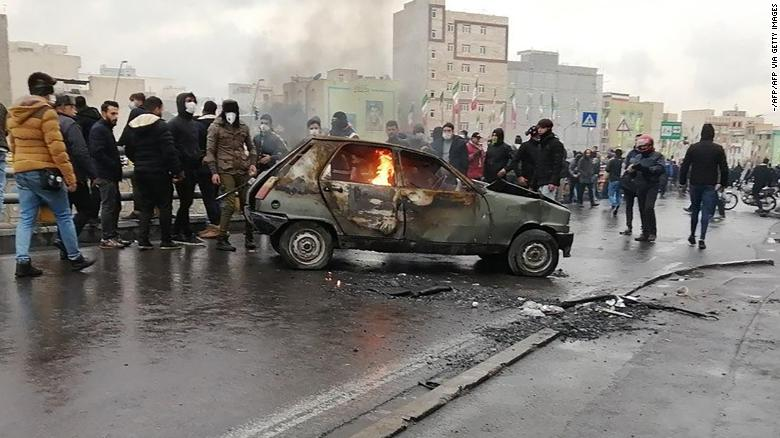 Iranian protesters gather around a burning car Saturday in the capital city of Tehran.