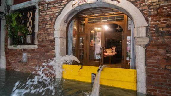 Pumps spout water from a flooded restaurant on November 17.