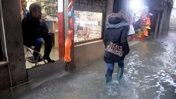 A man sits on a stepladder inside a shop as a woman walks down a flooded street.