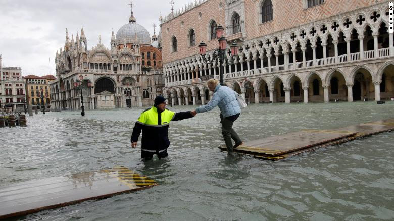 A city worker helps a woman cross a gangway in Venice, Italy, on Sunday, November 17.