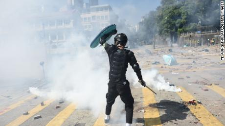 A protester responds with tear gas fired by police at Hong Kong Polytechnic University on Sunday.