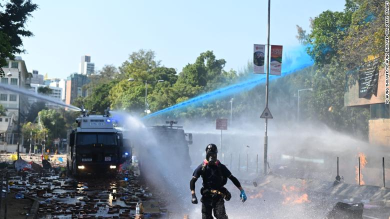 Police launch water cannons and tear gas outside the Hong Kong Polytechnic University in an attempt to disperse protesters on Sunday.