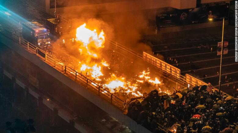 A police armored vehicle catches fire as protesters and police clash on a bridge at the Hong Kong Polytechnic University on Sunday night.