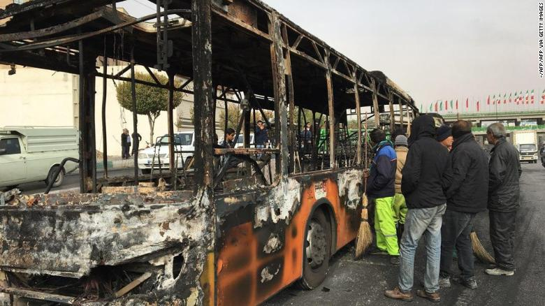 Iranians inspect the wreckage of a bus that was set ablaze by protesters in Isfahan on Sunday.