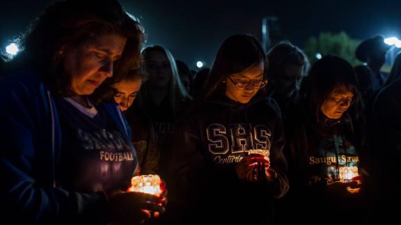 Yvonne Pane, Danielle Pane, Anh-Thi Ta and Ha Trinh pray while holding candles at a vigil in Santa Clarita on Sunday, November 17. More than 10,000 mourners gathered at the vigil at Central Park in Santa Clarita, the Los Angeles Sheriff's Department said.