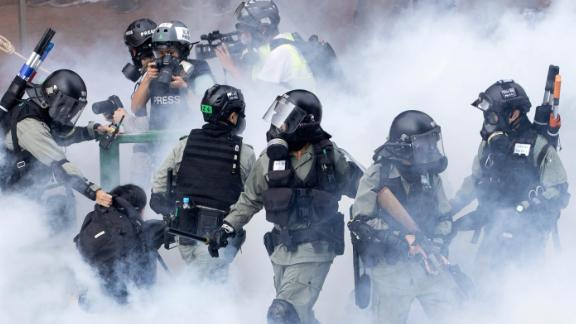 Police in riot gear move through a cloud of smoke as they detain a protester at the Hong Kong Polytechnic University in Hong Kong on November 18. Police have attempted to clear the university, which has been occupied by protesters for days as a strategic protest base.