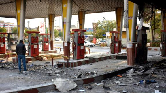 """An Iranian man checks a scorched gas station that was set ablaze by protesters during a demonstration against a rise in gasoline prices in Eslamshahr, near the Iranian capital of Tehran, on November 17, 2019. - President Hassan Rouhani warned  that riot-hit Iran could not allow """"insecurity"""" after two days of unrest killed two people and saw authorities arrest dozens and restrict internet access. Rouhani defended the controversial petrol price hike that triggered the protests -- a project which the government says will finance social welfare spending amid a sharp economic downturn (Photo by - / AFP) (Photo by -/AFP via Getty Images)"""