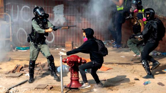 A policeman in riot gear points his weapon as protesters try to flee from the Hong Kong Polytechnic University in Hong Kong, Monday, Nov. 18, 2019. Hong Kong police have swooped in with tear gas and batons as protesters who have taken over the university campus make an apparent last-ditch effort to escape arrest. (AP Photo/Ng Han Guan)